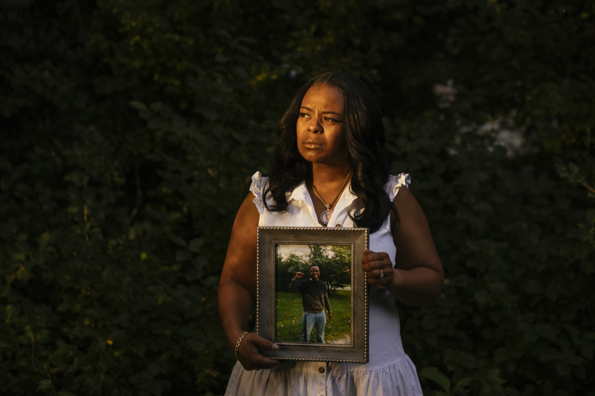 a black woman standing outside with the soft sunlight casting over her face as she holds a portrait of her son