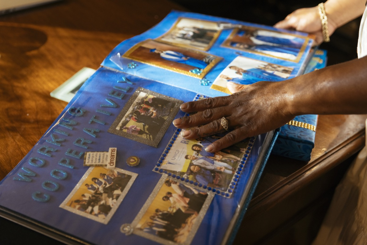 the hand of a black woman pages through a scrap book filled with photos of her son's life