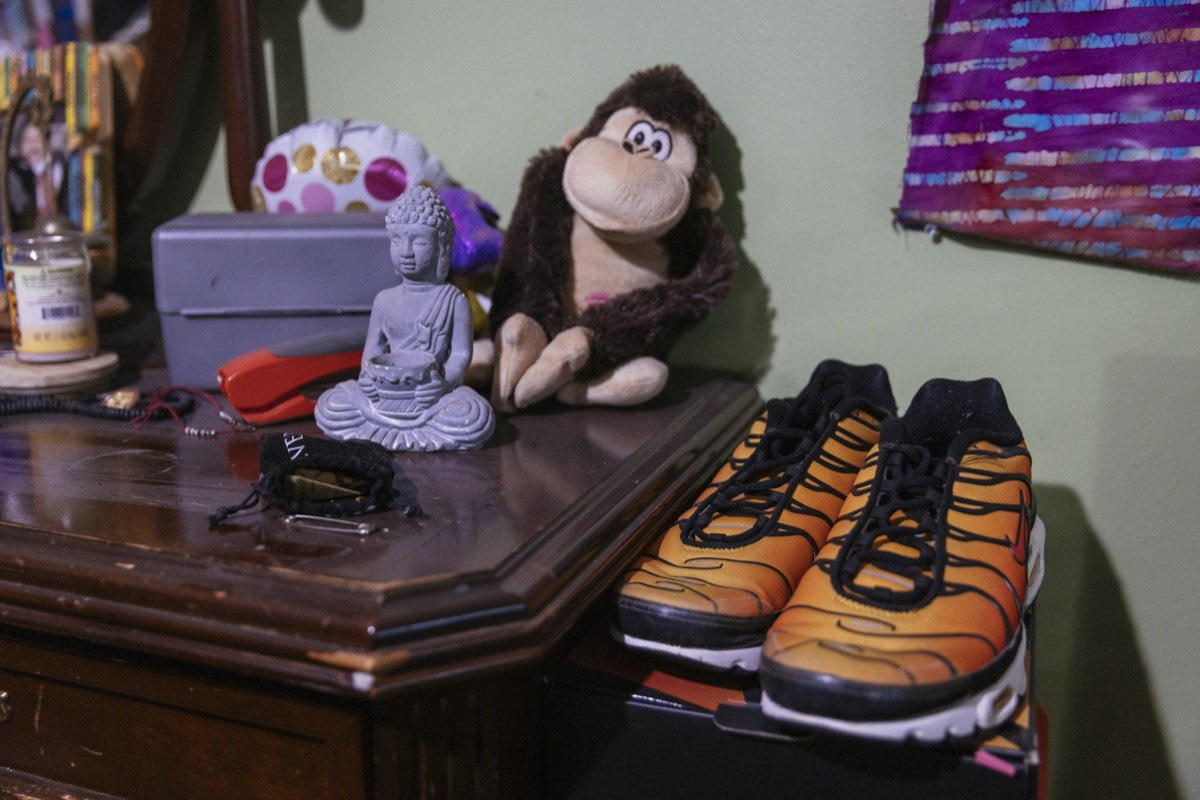a collection of items on a dresser, including a monkey stuffed animal, purple buddha statue, and yellow running shoes