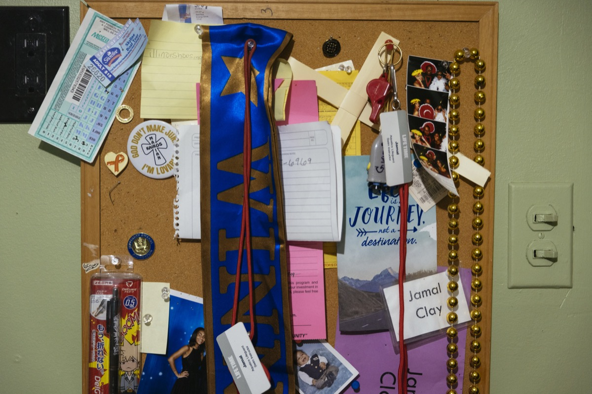a cork board on a wall with a variety of pinned mementos such as a school ribbon, beads, pins, cards, and aspirational notes