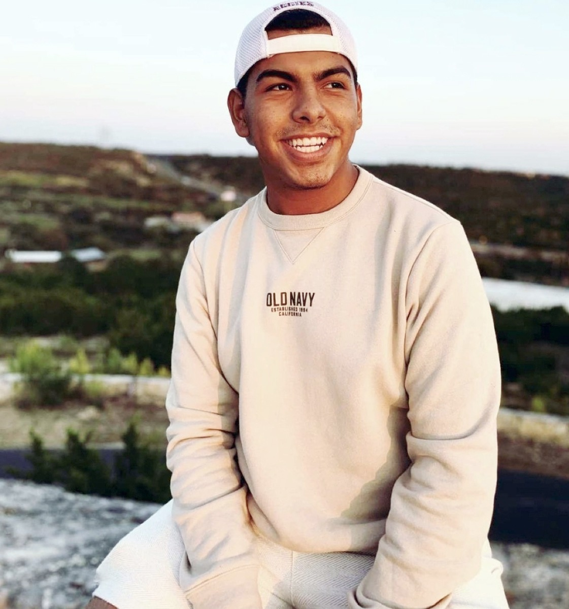 a young hispanic man in a white cap and cream sweater smiles sitting outside