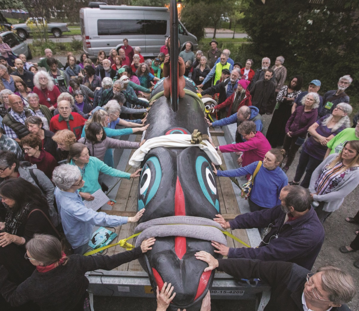 a group of people surround and carry a colorful painted totem pole of an orca