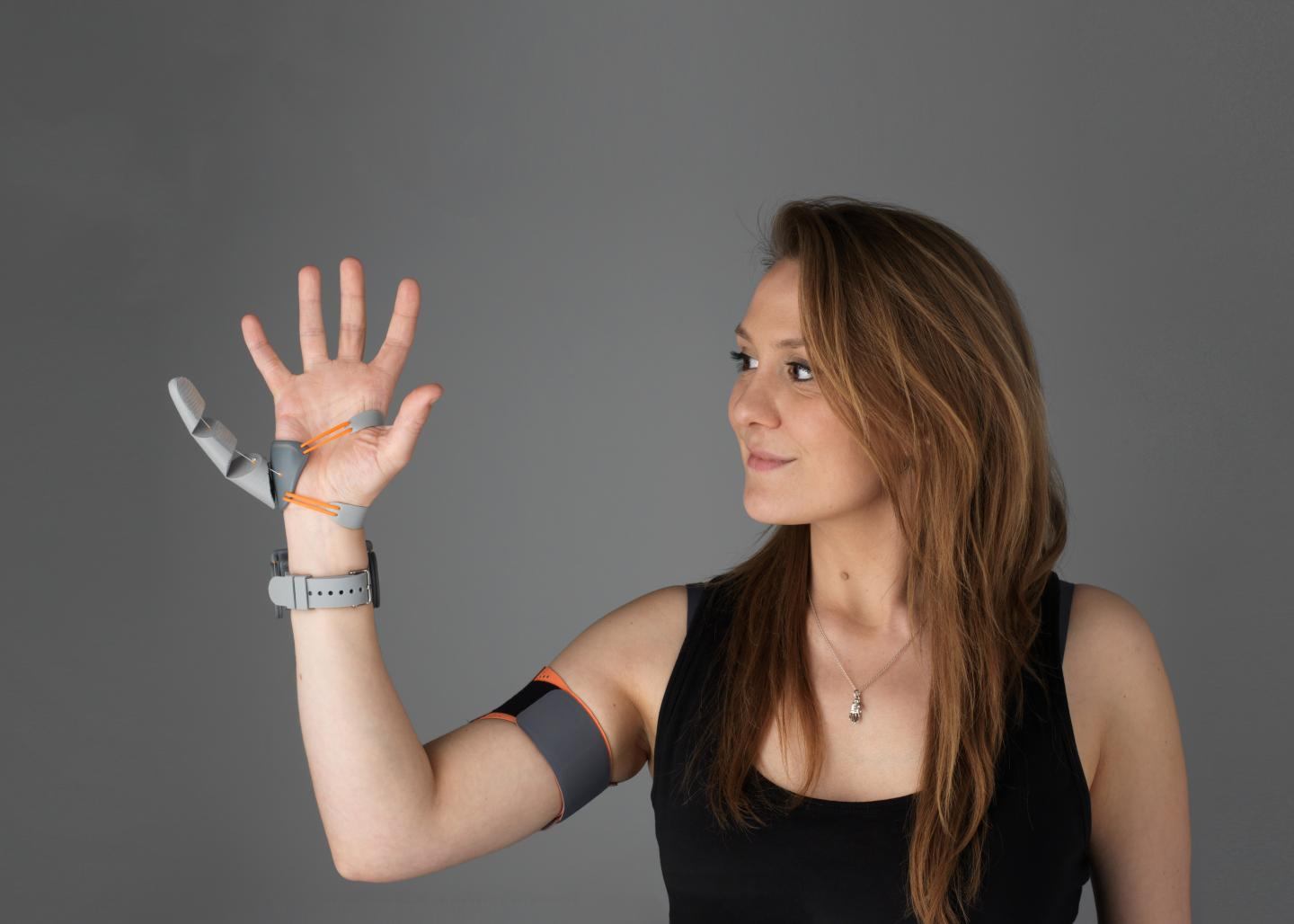 a white woman holds up her right hand. a prosthetic additional thumb is attached to the opposite side of her right hand, accompanied by some wires leading to a strap around her bicep