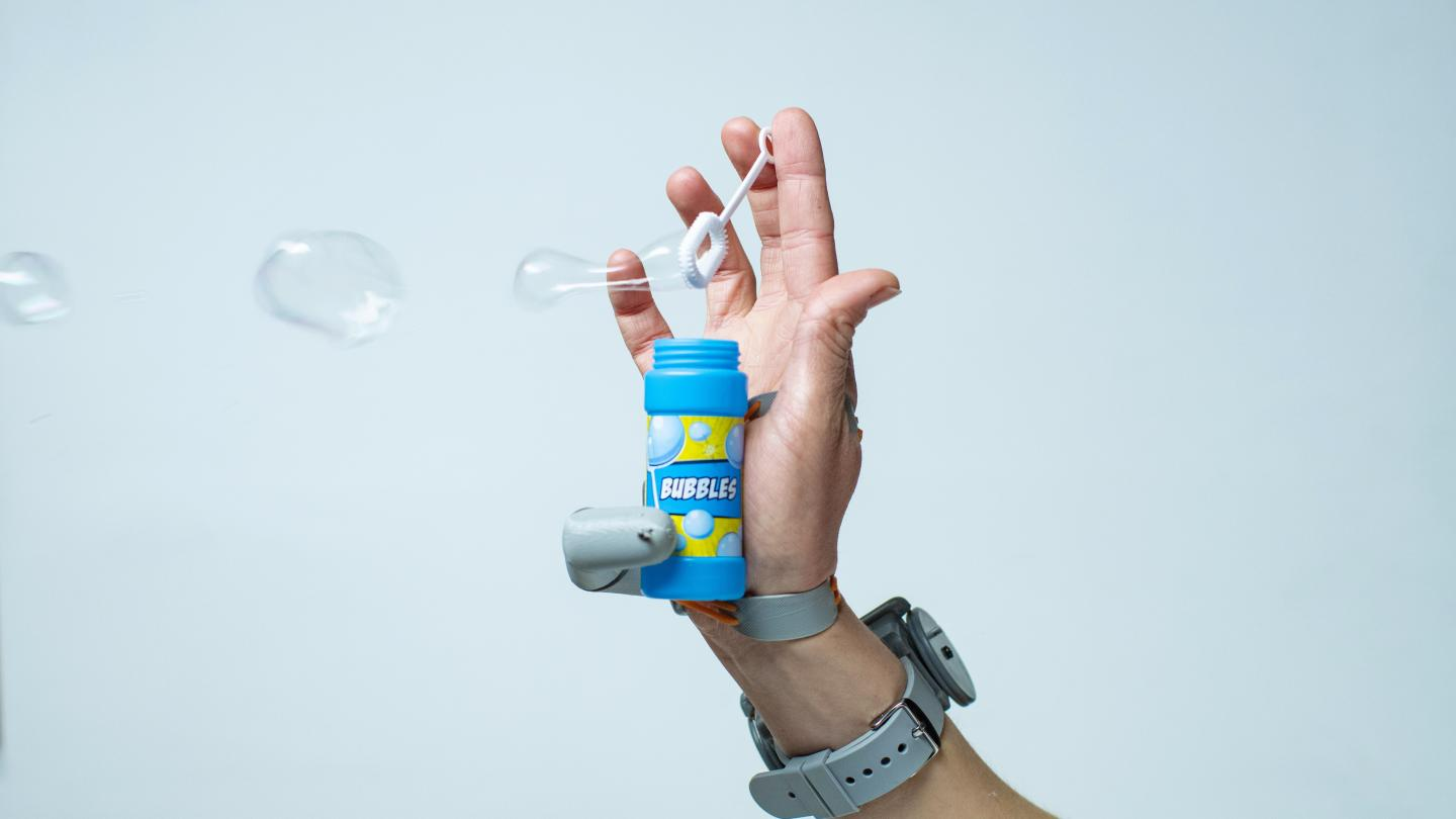 a white hand with the additional thumb prosthetic attached, allowing the user to hold a small bottle of blowing bubbles with the additional thumb while another finger holds the bubble wand