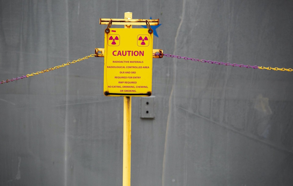 """a yellow caution sign that reads """"radioactive materials radiological controlled area DLR and SRD required for entry RWP required no eating drinking chewing or smoking"""""""