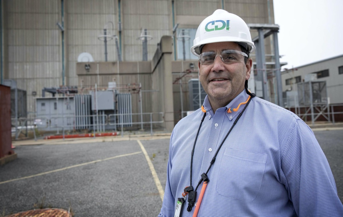 a man in a white hard hat wearing safety glasses and blue shirt stands in front of a power plant