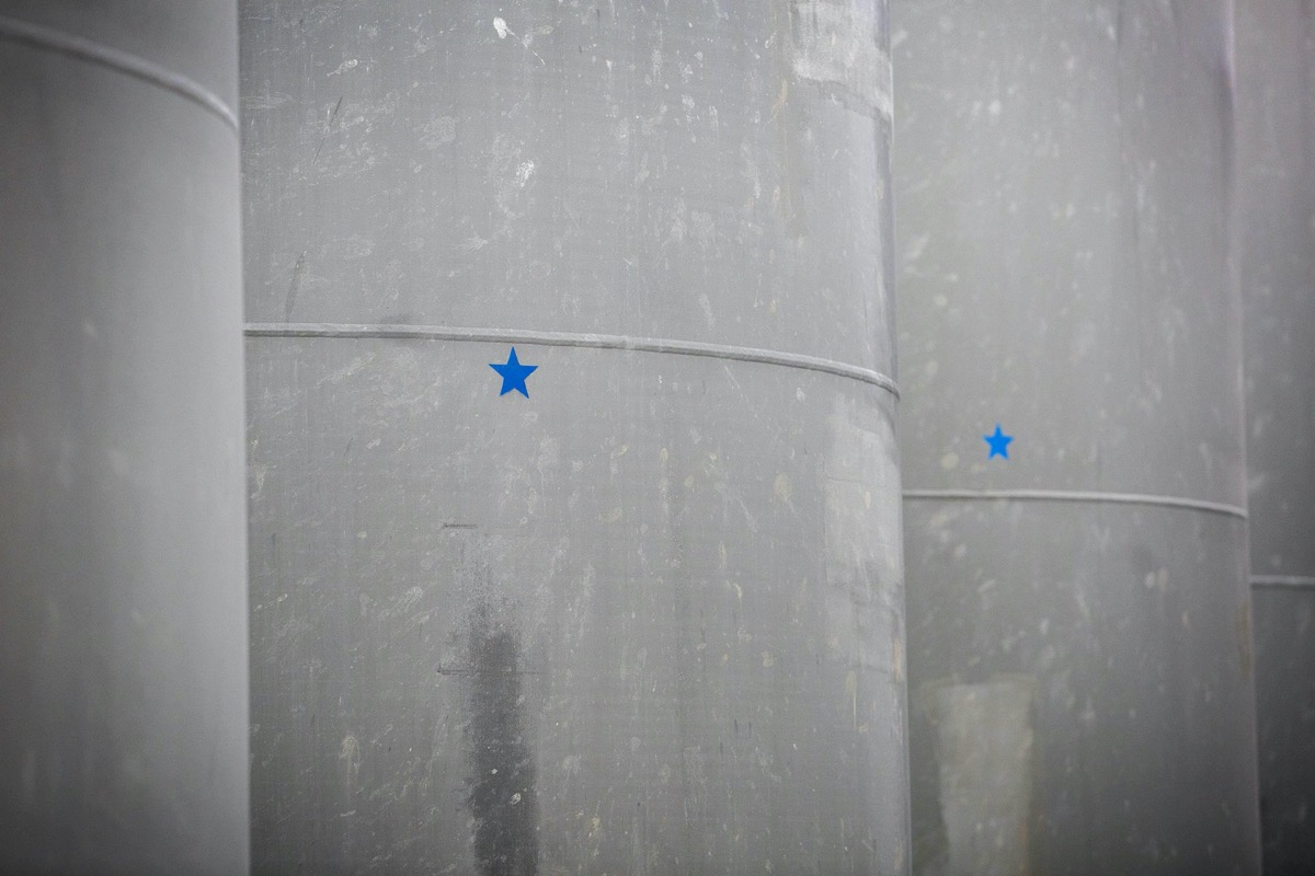 a close up on large gray cylinder casks, each with blue stars