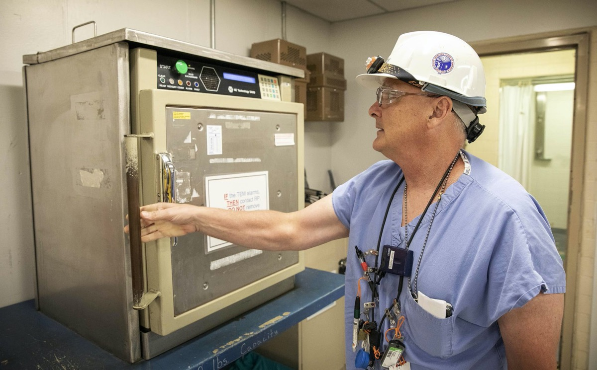 a man in safety glasses and a white hard hat wearing a blue surgical gown opening up a metal box