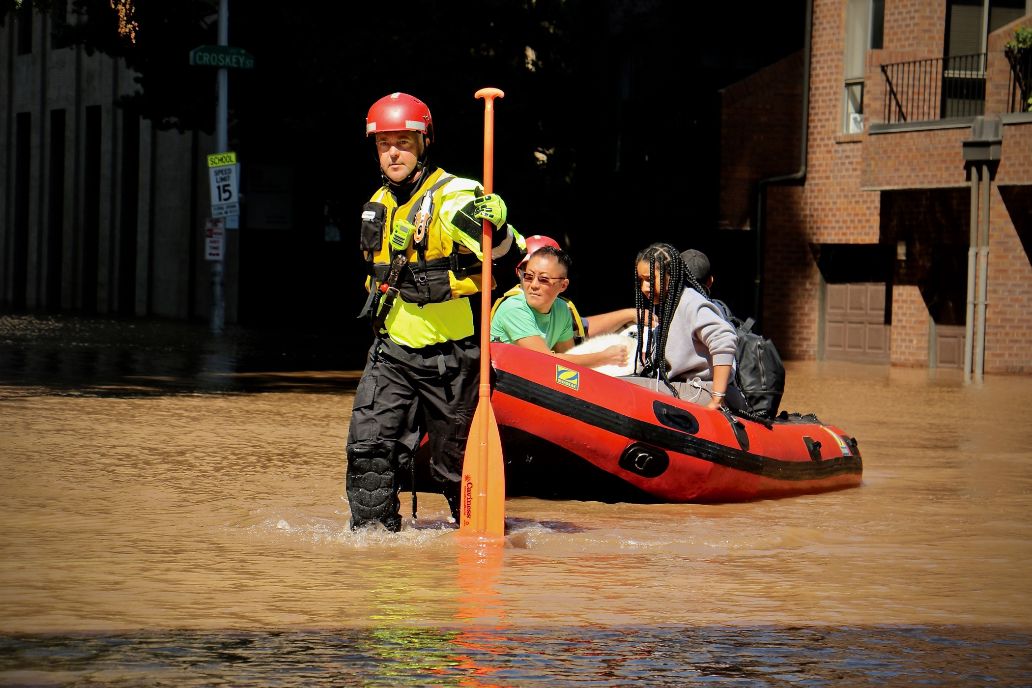 a white man in a hazard vest, hard hat, and water pants holds an oar with one hand and pulls a small inflatable rescue boat with four people in it through a flooded street. the water goes up to his shins