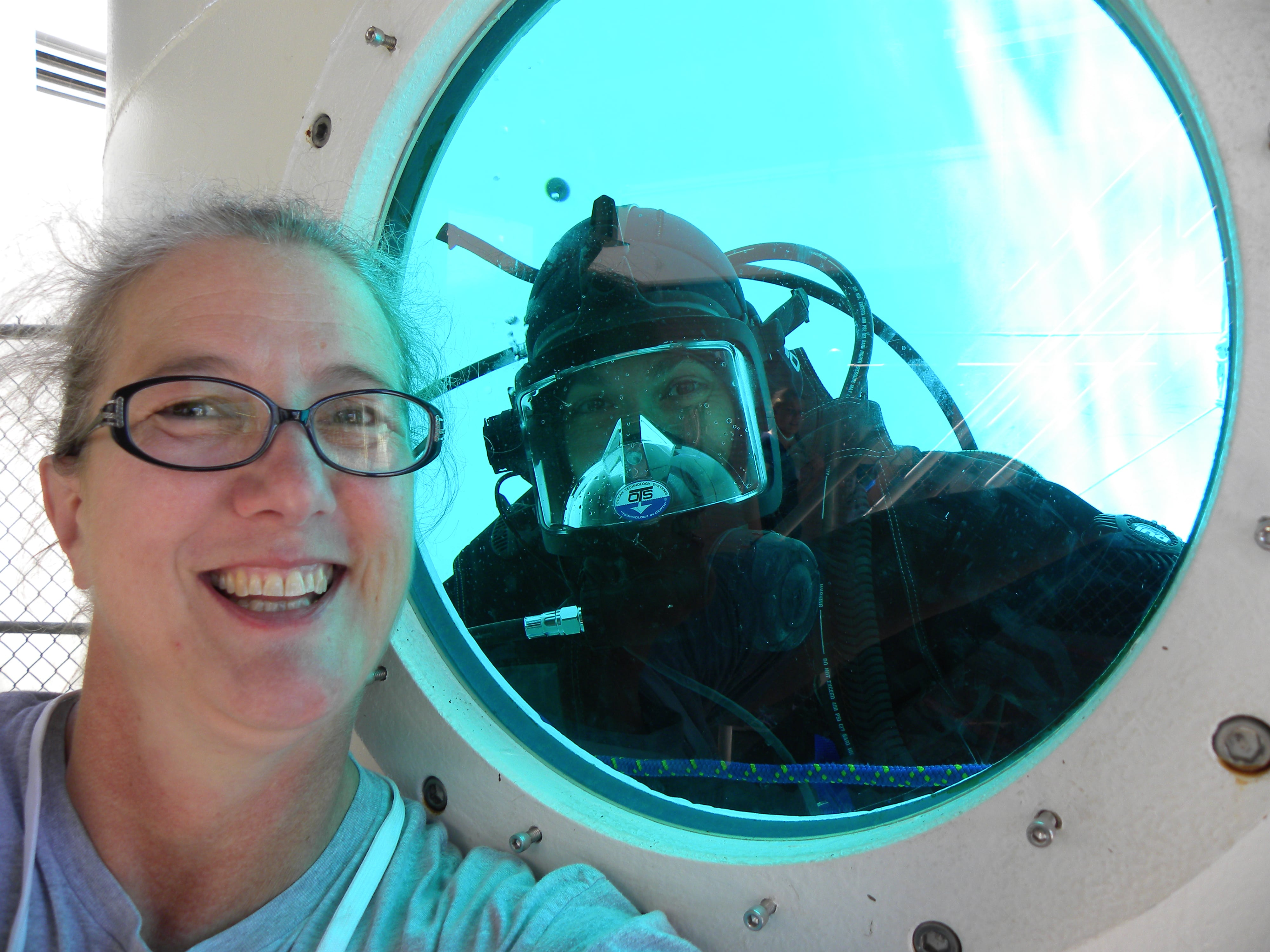 Diver in full scuba gear that the window of a training tank and educator Turtle Haste outside, selfie