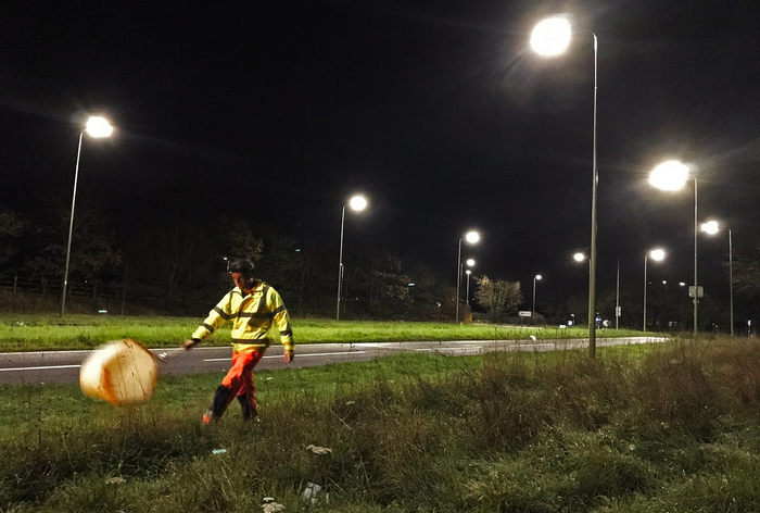 a person in a bright yellow jacket and orange pants swings a bug net along the side of a brightly lit road in the middle of the night