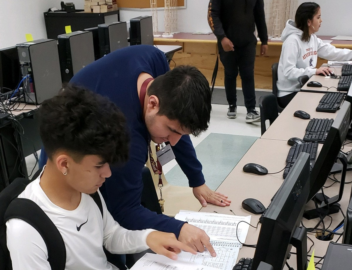 Educator Sergio Estrada and student looking at data on a paper. Two students in background.