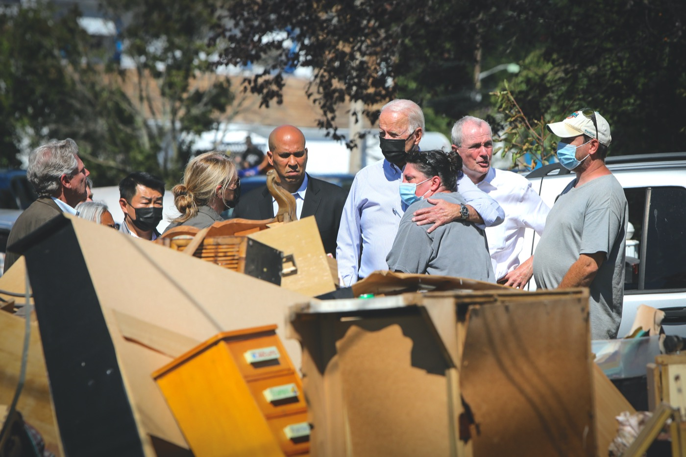 president biden comforts a white woman as they look on to wreckage and debris from hurrican ida. both of them are wearing masks a small group of people stand behind them