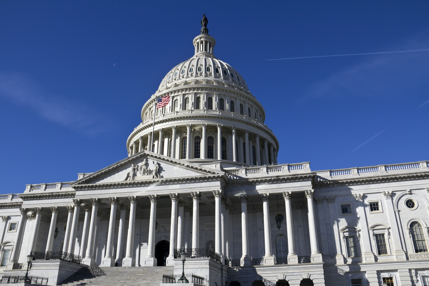 looking up at the u.s. capitol building on a cloudless day