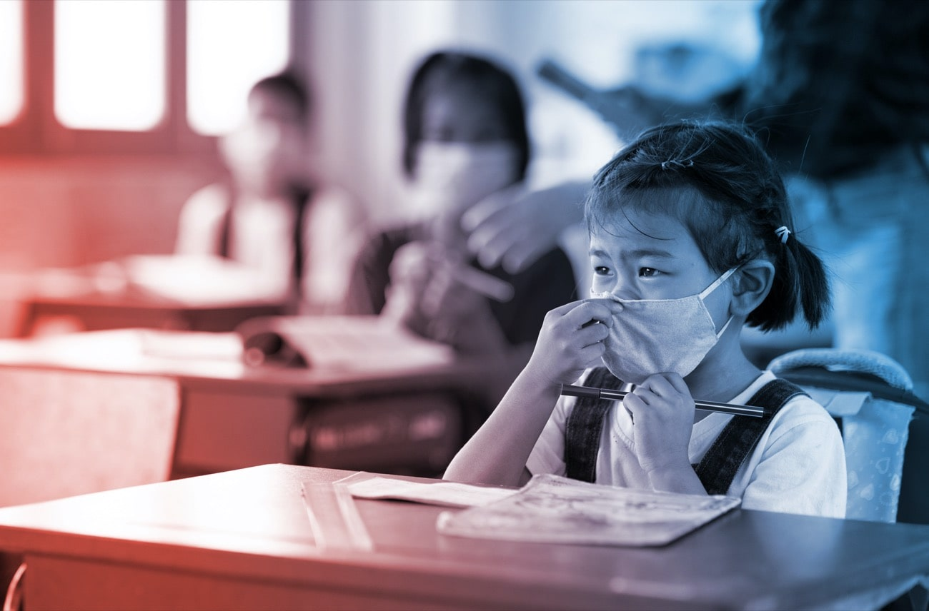 a young asian girl adjusts her mask with other students behind her and a teacher, all wearing masks