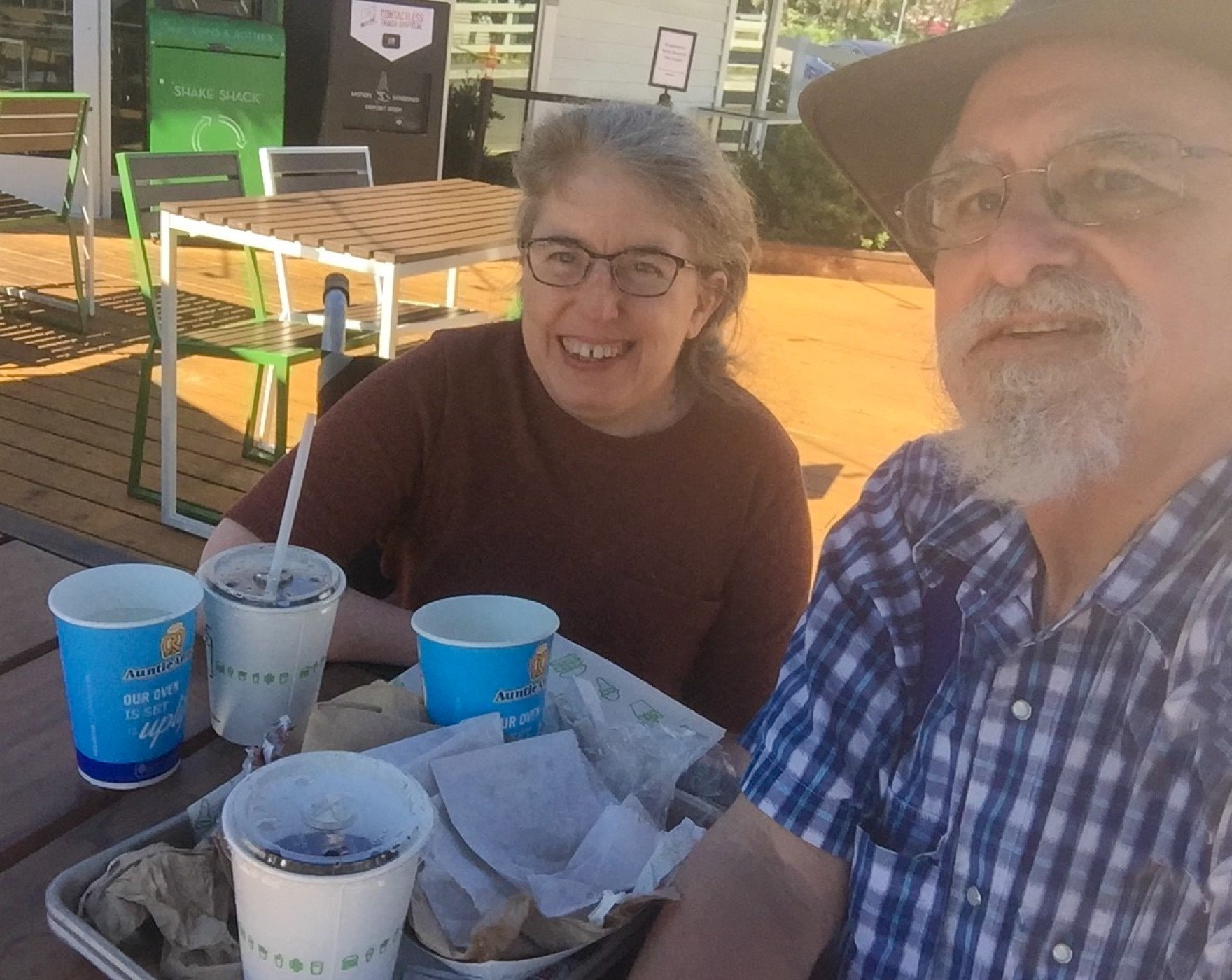 Ingrid and Ken are sitting next to each other, smiling, and looking into the camera. Ingrid is wearing a red shirt and Ken is wearing a blue checkered shirt. On the table are food trays, empty wrappers, and drink cups.