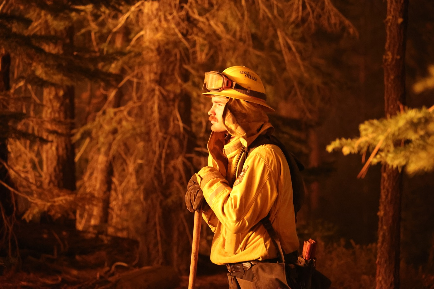 a side profile view of a white man with a moustache wearing a firefighter outfit with a helmet with goggles on it, leaning on a pole. its night and he's being illuminated by the orange glow of the blaze