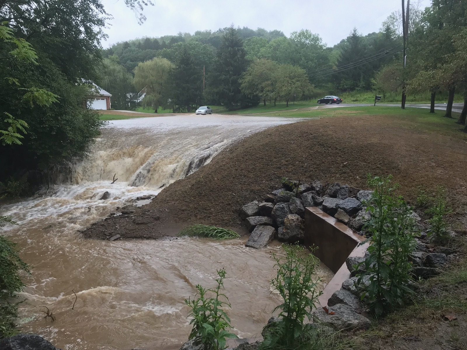 a waterfall of flooding going over a hill on a quiet residential street