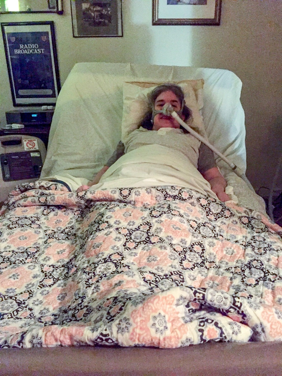 Ingrid is laying in bed with a mask and breathing tube attached to her face. She is looking directly at the camera. There is a pink floral bedspread on the bed and framed posters on the wall behind her.