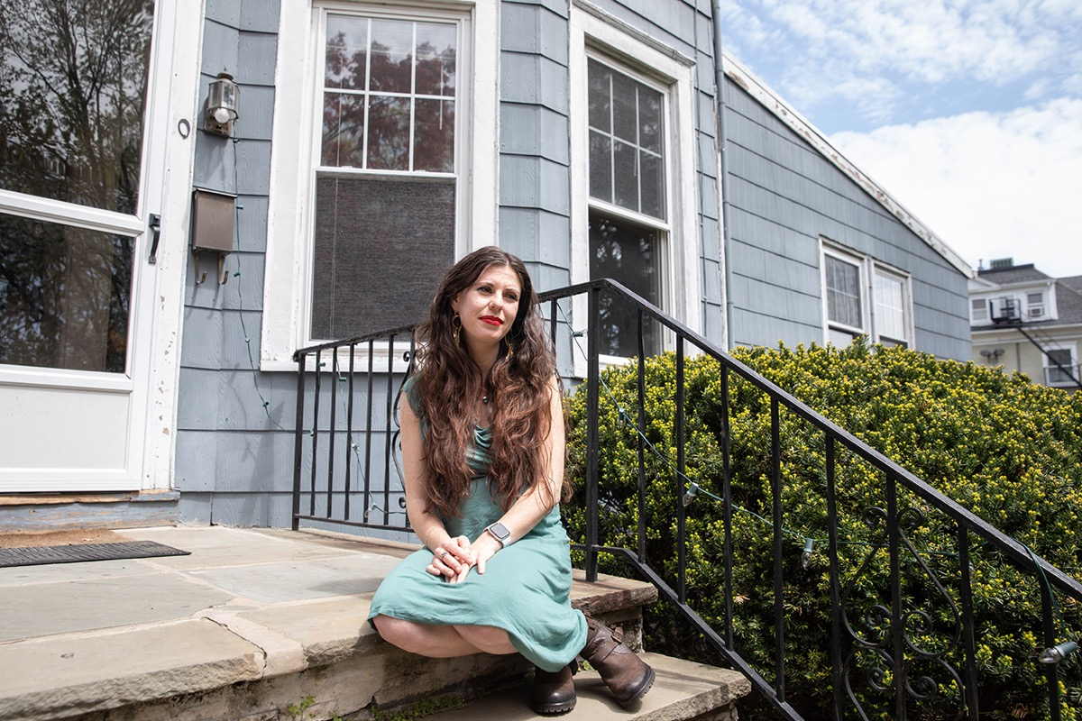 white woman sitting on steps outside of house, looking pensive