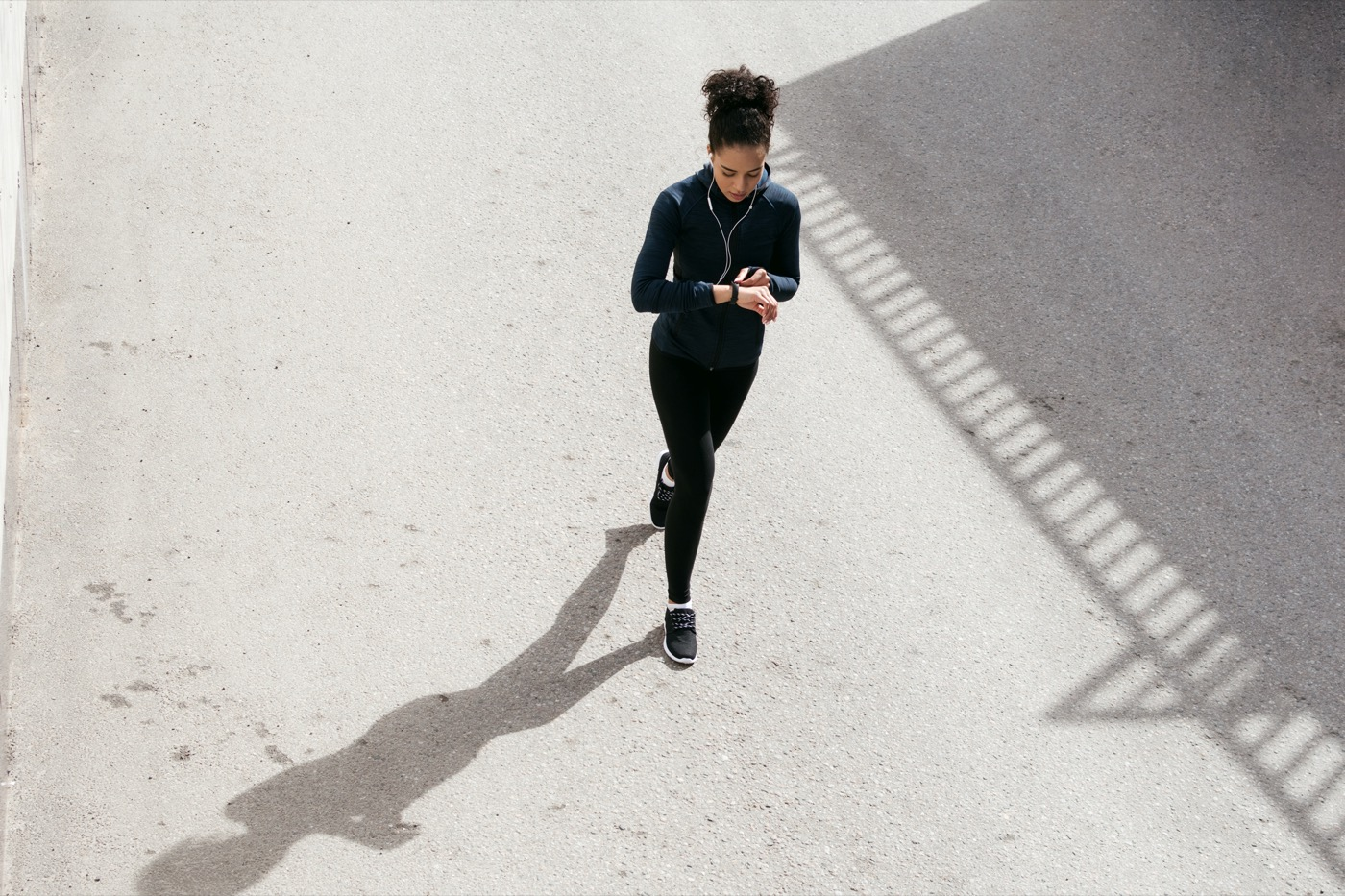 black woman walking outside in fitness clothing while checking her fitness tracker. its shot from above her