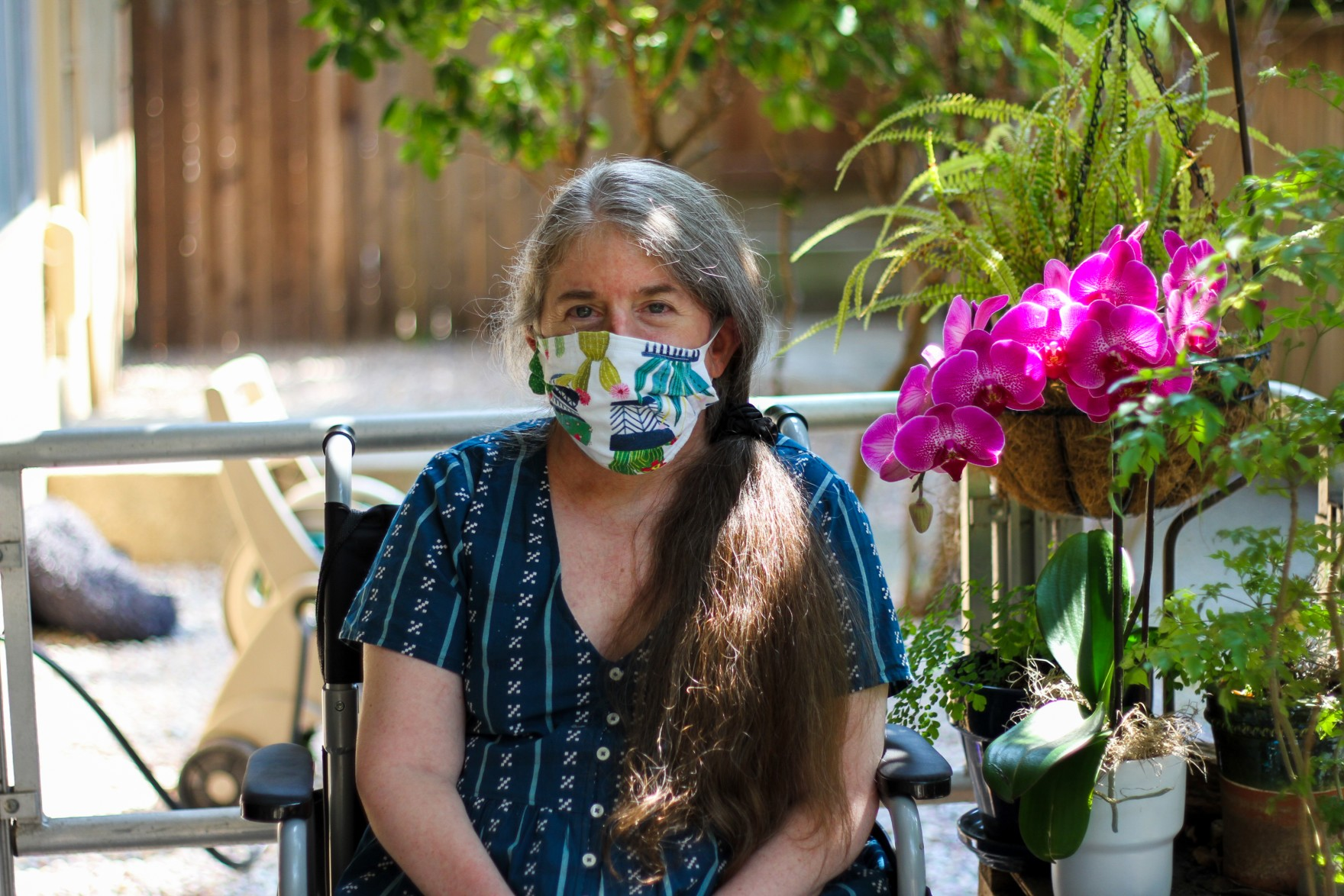 Ingrid, a white woman, is sitting in a chair on her front porch next to a bright magenta orchid. She is in her mid 50's and has gray and brown hair. She's wearing a white face mask with a plant pattern on it, and a patterned blue dress.