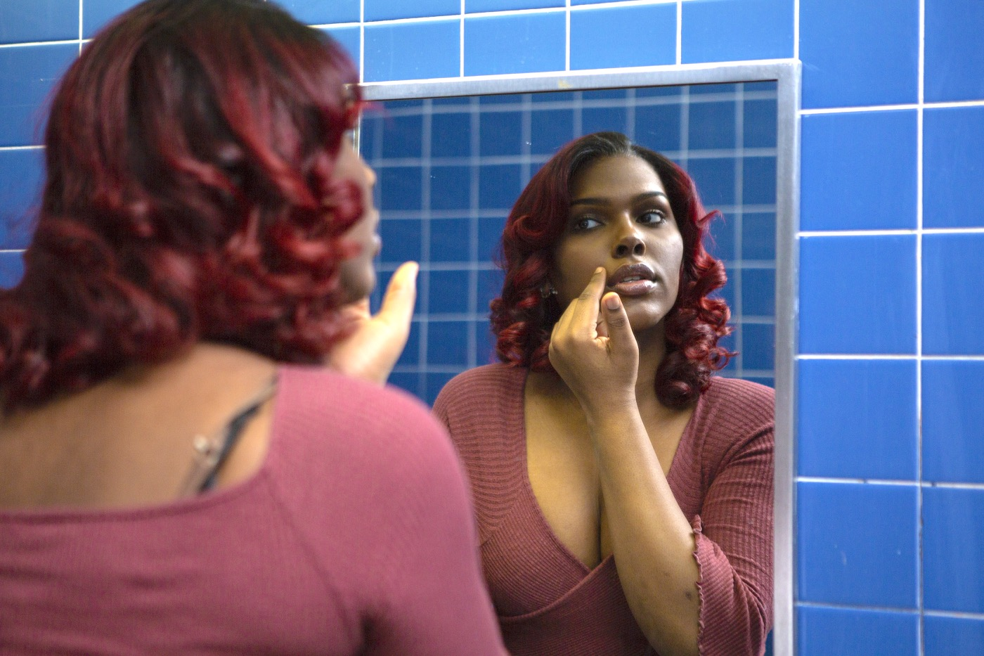 A black young transgender woman looking at her face in the bathroom mirror at school.